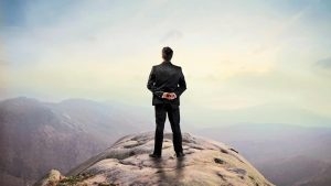 a man standing on an edge of the mountain looking at an endless horizon